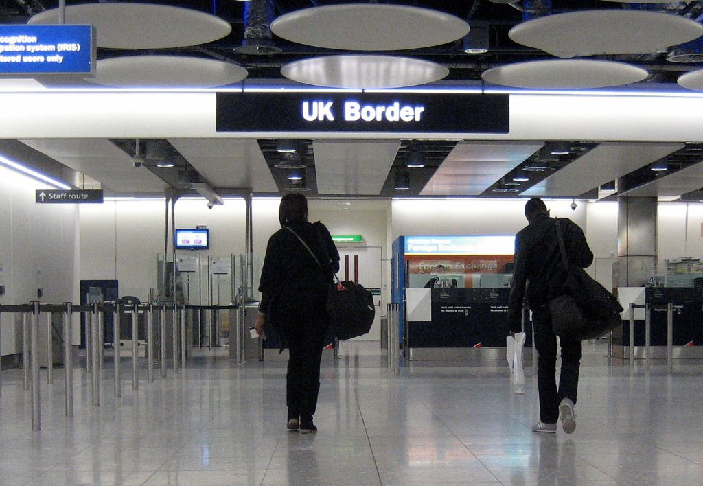 A picture of two people walking towards the UK border control at Heathrow airport. The border guards await them in perspex booths. Lines are made from barriers, but there's no crowd to contain.
